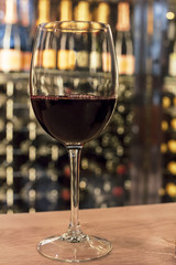 Red wine glass in front of blurred rack
