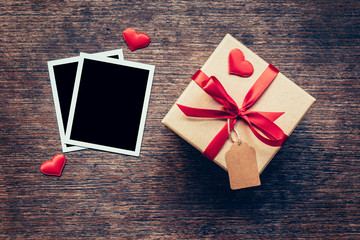 Blank photo frame and gift box with red heart on wood background