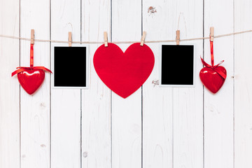 Two photo frame blank and red heart hanging on white wood backgr