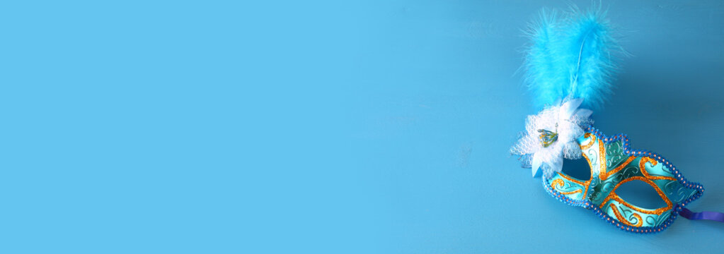 elegant venetian mask on blue wooden background