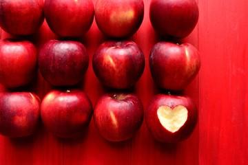 ハート型に皮を剥いた一個の林檎とたくさんの林檎 赤背景