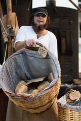 Fototapete - A man with a basket with bread