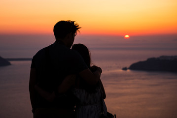 Couple in love looking at the setting sun on the most romantic island in the world - Santorini. Valentine's Day, Silhouette of men and women against the background of a romantic sunset