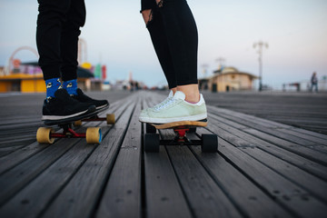 Young couple on the longboards, feet only