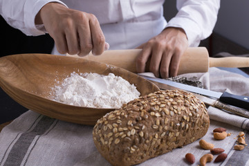 Whole grain bread put on kitchen napkin decorated with almond with a chef holding dough roller at the background.