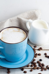 a cup of cappuccino and a milk jug on the wooden background