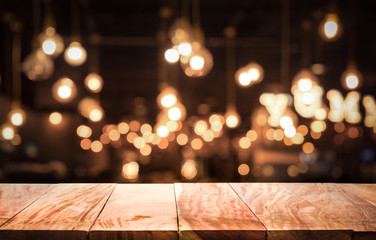 Wood table top on blurred of cafe ( restaurant ) with light gold bokeh