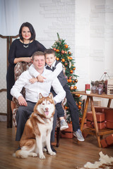 mother, father and little boy with Husky background Christmas tr
