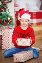 Boy with xmas gifts on wooden background