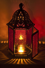 Metal Vintage Lantern lit by candlelight with deep red and gold colors/Metal Vintage Lantern illuminated by candle light with brilliant red and gold tones. Patterns of light spill all around it