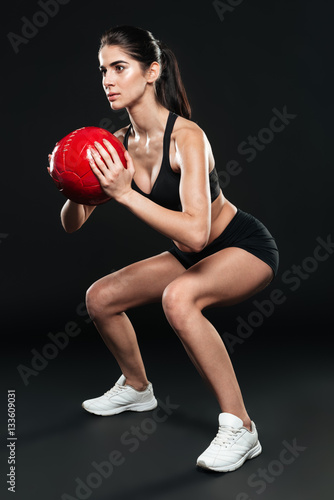 Young fitness woman doing squats with weight