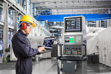 Engineer using laptop computer for maintenance equipment in powerhouse