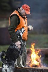 Man with dog at campfire