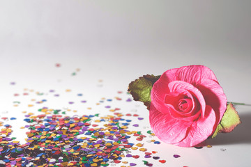 Artificial pink roses on a gray background with heart colorful glitter