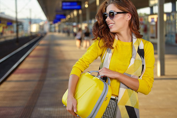 summer travel, woman with suitcase waiting for her train on plat