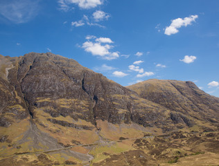 Glencoe mountains tourist attraction Scotland UK in Scottish Highlands in spring with blue sky and sunshine