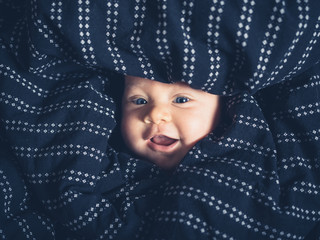Happy little baby under the bedsheets