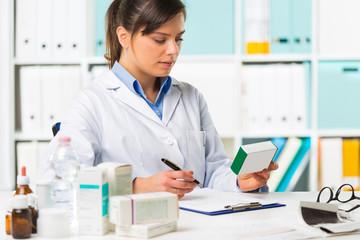 Female pharmacist sat at desk writing notes