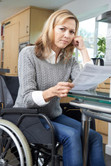 Frustrated Woman In Wheelchair Reading Letter