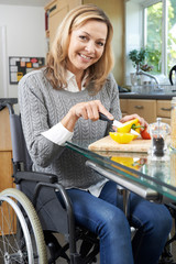 Woman In Wheelchair Chopping Vegetables In Kitchen