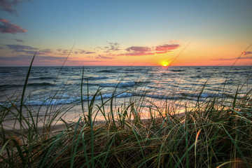 Scenic Summer Sunset Background.  Beautiful sunset horizon over water with a sandy beach and dune grass in the foreground. Hoffmaster State Park. Muskegon, Michigan.