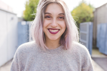 Portrait of young beautiful caucasian purple grey hair woman outdoor in the city looking at camera, smiling - happiness, carefree, serene concept