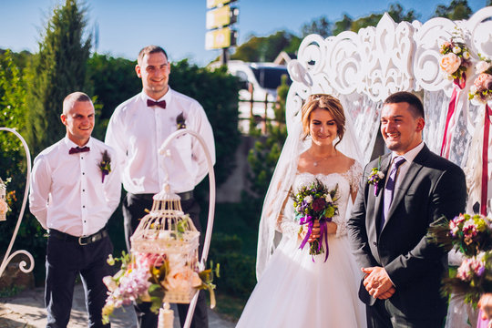 Bride and groom on wedding ceremony near decorated arch and photozone outdoor