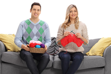 Young man sitting on sofa and helping young woman knit