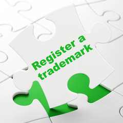 Law concept: Register A Trademark on puzzle background
