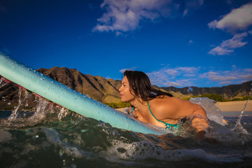 Hawaiian surfing girl paddling into the ocean. Water splashes around surfing board. Blue sky with green mountains at background