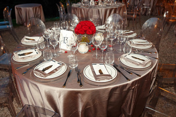Silver cloth covers round table served with sparkling glassware