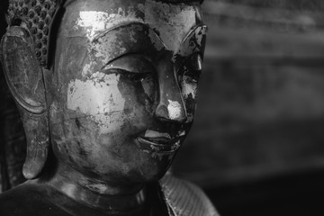 close up face on buddha head statue and black and white image style. Selective focus face buddha statue.