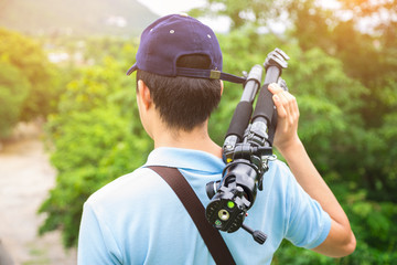 A photographer or traveller with a camera tripod in the nature f