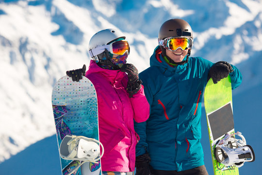 Happy couple of snowboarders in the alpine mountains