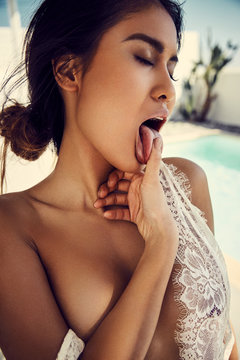 asian girl licking her finger in front of a pool