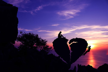 Women sitting and Men climbing on broken heart-shaped stone on a mountain with purple sky sunset background.Silhouette Valentine background concept.