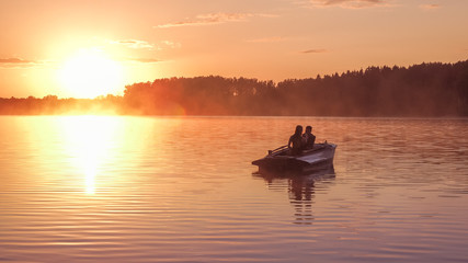 Romantic golden sunset river lake fog loving couple small rowing boat Romantic date beautiful Lovers ride boat during beautiful sunset Happy couple woman man together relaxing water nature around