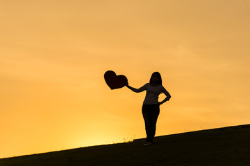 Silhouette of asian lady standing on hill and holding heart with one hand on the side during sunset time to show her love on Valentines day