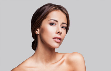 Studio portrait of a beautiful young woman with brunette hair. Pretty spa model girl with perfect fresh clean skin. Youth and skin care concept