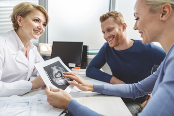 Extremely happy future parents coming to doctor