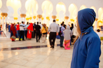 Woman in blue hood looks over her shoulder at people walking to