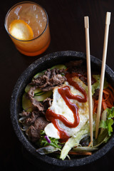 Bibimbap bowl with chopsticks and drink, overhead view