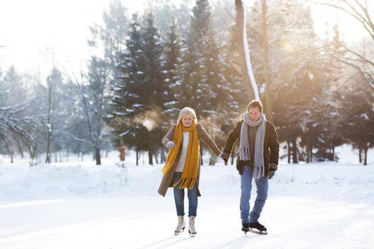 Senior couple in sunny winter nature ice skating.