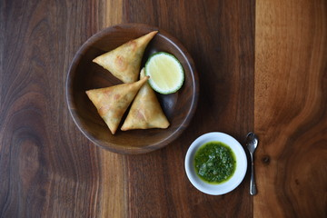 Baked samosa in wooden bowl on table, overhead view