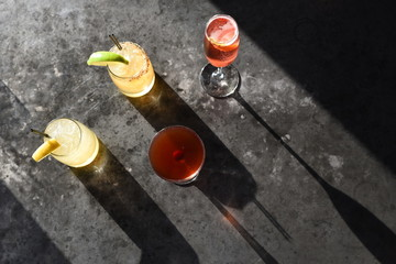 Drinks in cocktail glasses on concrete surface