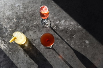 Drinks in cocktail glass on concrete surface, overhead view
