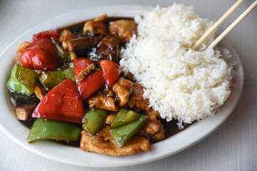 Stir fry with rice and chopsticks on plate