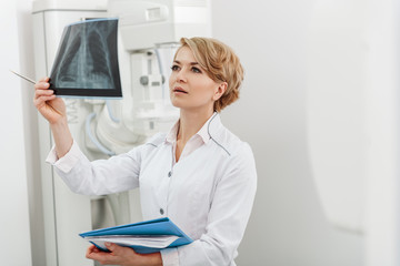Interested female doctor holding radiograph