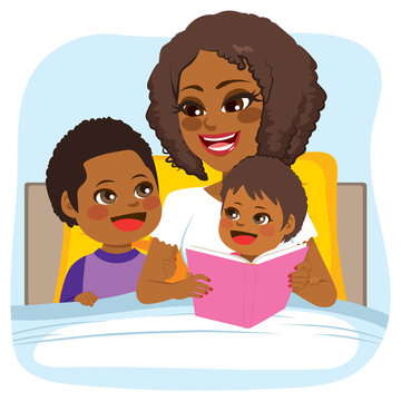 Young African American mother reading bed time tale story to son and daughter on bed