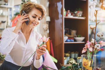 Happy female florist talking on smartphone